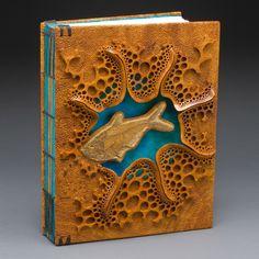 """Mark Doolittle. """"Fossil Fish Book"""" 13""""h x 10""""w x 2""""d. Afzelia Burl with inlayed fossil fish. Binding by Kathy Doolittle."""