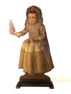 This wooden painted figure standing alone shows a girl holding a doll. It looks as if the figure has been cut out of a provincial Spanish portrait of about 1600 and then mounted on an ebonised wood base. These type of pictures are not really paintings but form part of the furniture, called dummy boards or 'silent companions' and are supported by a stand. They were usually found in entrance halls of houses, as greeters, or in front of fireplaces and acted as firescreens. At Castle Drogo…