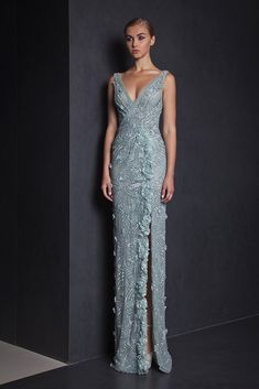 Fully embroidered Watergreen evening gown with V neckline and a side slit, embellished with Lace flower detailing on the side.