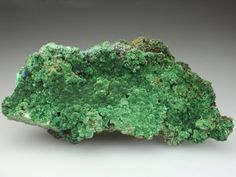 An excellent specimen of Olivenite from the Christiana Mine, Lavrion, Greece. The Olivenite 95% covers the small amount of matrix, in a rich druse of intergrown radial crystal clusters. The Olivente has a pleasing light to deep green colour. Areas of blue Azurite are associated with the Olivenite at one edge of the specimen. Asuperior specimen of Olivenite from the mine.