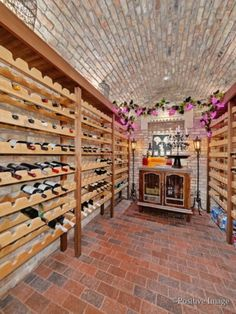 Wine cellar with brick floors and an arched brick ceiling and an alcohol cabinet at the end