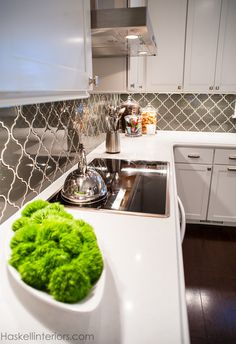 An arabesque styled smoky grey glass backsplash adds drama and contrast to this white kitchen. Natural quartz countertops provide a practical yet beautiful countertop.  Kitchen Renovation by Haskell Interiors featured in Signature Kitchens & Baths Magazine