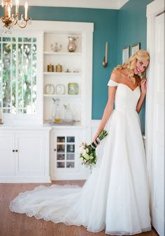 Silk Organza.  Natural waist A-line gown with side box pleats and cathedral length train.  Sweetheart neckline with off the shoulder organza sleeves.