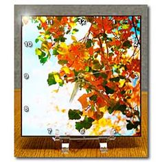 A close up of some leaves hanging from a tree in fall colors Desk Clock
