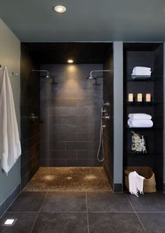 curbless shower with small rock looking floor and white towels as a finishing touch.: