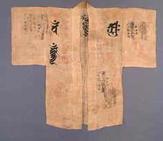 Suzukake  Japon XIXe siècle Toile de chanvre, calligraphie, sceaux  Ce Suzukake est un manteau de Shûgenja, moine pèlerin du bouddhisme ésotérique menant une vie d'ascète dans les montagnes. D'une coupe droite, c'est un exemple dans lequel, la grossièreté du matériau et la simplicité du tissage sont un moyen de mettre en valeur l'importance du message religieux transmis par la calligraphie, transformant alors ce costume en mandala ou diagramme mystique.