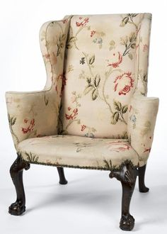 Wing chair  A wing armchair in walnut with brocade upholstery, made in England about 1720. It has scrolled arms and cabriole rear legs with club feet. The massive cabriole front legs have shell ornament, with ball and claw feet. It is upholstered in a cream coloured (originally pale pink) floral cotton and silk brocade.