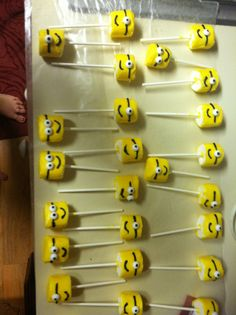 Minion marshmallow pops! I use regular sized marshmallows. First, melt yellow candy melts down. Use small, pointed offset spatula to scoop and smooth out the candy around the marshmallow. Let dry. I used black cookie icing for the mouth and eye bands and candy eyes. Let dry for around 45 mins-1hr. Check to make sure candy is completely dry before handling. Wrap in plastic treat bags and tie off with blue ribbon