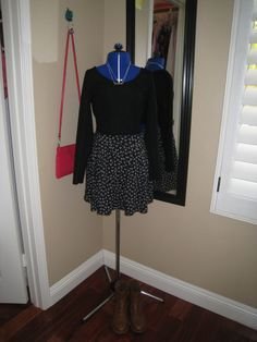Black crop top, and black and white skirt with a pop of red in the purse