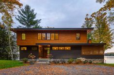 A warm yet inviting modern lake cottage in Canada used for entertaining Lakeside Cottage, Lake Cottage, Modern Contemporary Homes, Wood Front Doors, Built In Grill, Wood Siding, House Made, Outdoor Rooms, Outdoor Seating