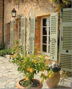 Oh so Provencal - lemon trees, pale shutters, stone walls, hanging lanterns, flagstone walkway