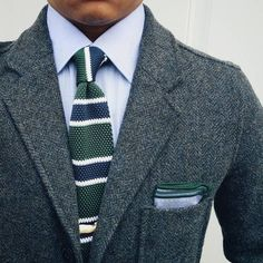 Dark grey tweed jacket, light blue shirt, green knit tie with blue & white stripes