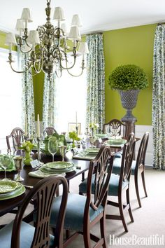 The verdant dining room of a Long Island home features walls painted in Benjamin Moore's zesty Grenada Green and curtains in Quadrille's Forbidden City fabric. Dining chairs are covered in a velvet by Schumacher. Antique chandelier from Meg Braff Designs.