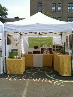 "I love the chalk drawing on the street  in front of this outdoor craft show booth that says ""welcome"""