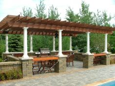 A spacious cedar pergola with built in BBQ, bar top space, and outdoor dining area. By Signature Outdoor Concepts