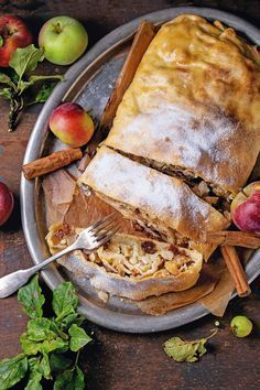 Sliced homemade apple strudel served with fresh apples with leaves, cinnamon sticks and sugar powder on vintage metal tray with fork over old wooden background. Montenegro, Apple Strudel, Metal Trays, Fresh Apples, Culinary Arts, Cinnamon Sticks, Food Photography, Turkey, Food And Drink