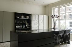 Minotti kitchen with streamlined cupboards and granite island with concealed storage