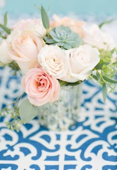 Creamy pink roses on a contrasting table cloth create a striking summer setting.