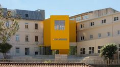 Aurora Arquitectos has united two classrooms blocks at the Artave music school with a bright yellow extension and stair tower.