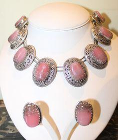 Splendida e rarissima parure con girocollo e orecchini a clips, con grandi elementi in metallo argentato lavorato a traforo, sui quali sono incastonati dei cabochon in vetro artistico rosa. Francia, anni '60.