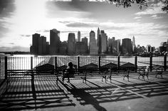 A girl is sitting on a bench on Brooklyn Heights Promenade, facing the Wall Street skyline, Brooklyn, New york