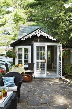 This cottage's black-stained wood siding and crisp white gingerbread trim were left untouched to keep the original authenticity and charm of the structure. The stone patio offers space for comfortable, lazy afternoons in the shade.