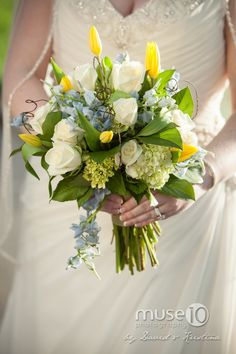 A romantic mix of whites, soft blues, pops of yellow, and greenery.   Bridal bouquet by Twigs in Greenville, SC