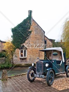 Old British Farmhouse - An old British farmhouse with a very old car outside.