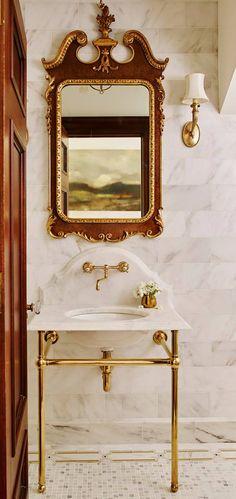 Precioso baño con azulejos en suelos y paredes, mucho mármol, madera y detalles dorados.