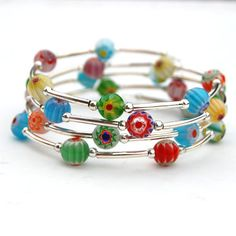 This bright wrap bracelet is made from multi coloured round millefiori beads and silver spacer tubes on memory wire. It would make a lovely gift or colourful winter accessory. I have used 8mm millefiori glass beads with silver plate spacer tubes and tiny silver plate seed beads. Because I