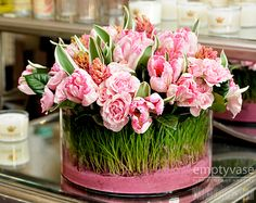"""Pink Tulips Dream  Description:This stunning arrangement is designed with pink Dutch Tulips, Spray Roses, Hyacinth and local wheat grass all arranged in a 10"""" x 4"""" low cylinder vase filled with pink sand. This arrangement is approx. 10"""" tall."""