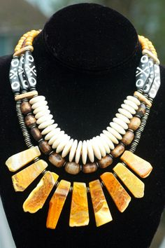 Exotic Tribal Brown Bone, Shell Disc and Amber Agate Fringe Necklace | XO Gallery  •Exotic tribal design batik bone  •Mother of pearl shell discs  •Batik brown bone from Kenya  •Amber agate fan cut stones  •African brass  •Mustard olive wood  •Amber horn  •Dutch gold resin donuts  •Brass lobster clasp  $350