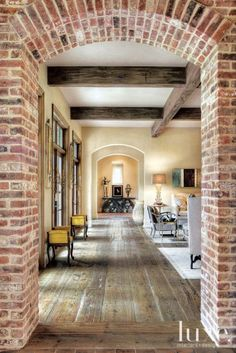 A table made of antique Gothic Revival arches leads the eye through a hallway that passes through the great room and by two 18th-century benches from Kirby Antiques on the way to the front door. Reclaimed wood flooring from Custom Floors Unlimited in Houston provides consistency throughout and works well with the abundance of antiques.