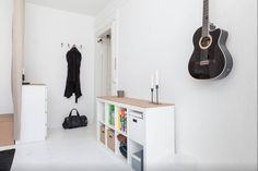 Introducing: Our designer Joao from Berlin. Pictured here is Joao's minimalistic DIY apartment. We love the simple and bright hallway which is a perfect example for minimalistic style. Great interior decor: the black guitar hanging on the wall. Click to find more inspiration!