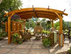 Rattan Chairs and Concrete Fireplace Decorated with Potted Plants Shaded by Classic Wooden Pergola in Traditional Patio Design Ideas