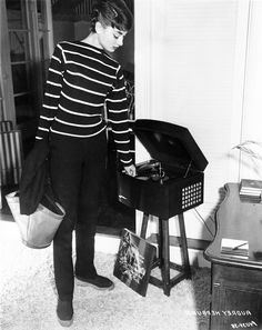 Audrey Hepburn photographed at her Los Angeles apartment listening to one of her jazz albums, 1953.