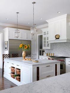 Walnut serving trays tucked into the vertical niches of the center island add dark contrast to an otherwise all-white kitchen.
