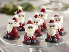Strawberries decorated to look like santas with coconut and blueberries