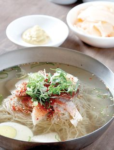 Naengmyeon - National dish of North Korea. Noodles in iced broth served with cucumbers, Korean pears, radishes and boiled eggs.