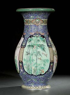 A CLOISONNÉ VASE  SIGNED TAMURA, MEIJI PERIOD (LATE 19TH CENTURY)  Worked in various thicknesses of silver wire and coloured cloisonné enamels with shaped panels depicting birds and flowers including swallows among irises, pheasant among wisteria and peacocks among plum blossom, bordered by stylised flowers and scrolling foliage and lappets to the footrim, silver mounts 31cm. high