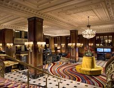 """The Blackstone hotel in Chicago features swirling rainbow colored carpet and gold couches amid original iron railings with the letter """"B"""" engraved from the original structure."""