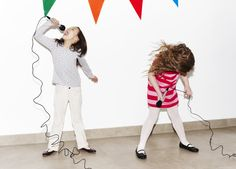 Girls singing into microphones at party