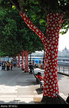 """""""Ascension of Polkadots on Trees"""" by artist Yayoi Kusama at the Queen's Walk along the Thames river, London, UK - Stock Photo"""