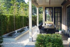 Garden, like patio and water feature on gravel with bush backdrop.