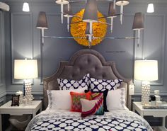 Gray walls with printed bedding and modern lighting fixture in jonathan adler bedroom