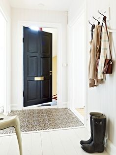 I was never really one for black doors inside a house, but after seeing these pictures I have completely flipped! I love how the contrast of a black door and white walls create an impactful Cemento Portland, Dark Doors, Inside A House, Industrial Style Kitchen, Tadelakt, Entry Hallway, Tile Entryway, Vintage Tile, White Walls