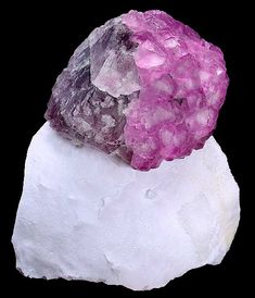 Unique specimen featuring a large modified Fluorite cube with a secondary growth layer of raspberry-colored Fluorite crystals. All sit atop a stark white Quartz matrix.