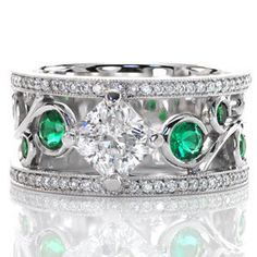 Design 2312 - Vivid green emerald side stones are bezel set into the large scroll of the filigree pattern. The 1.00 carat radiant cut center diamond is kite-set to continue the flow of the filigree. A row of micro pavé adorns both sides of this wide band ring with milgrain texture to accent the edges.
