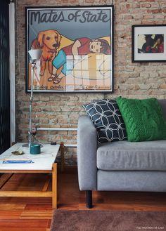 sala de estar com parede de tijolinho rústico e móveis com estilo industrial