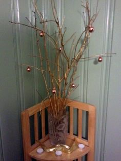 New Years Eve Arrangement. I literally took twigs from the yard and spray painted them gold, put them in a vase I already owned, and hung mini gold Christmas ornaments on the branches. (Our theme was black and gold).